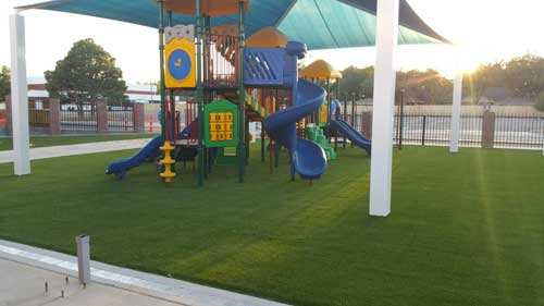 Sun rays on colorful playground with turf system