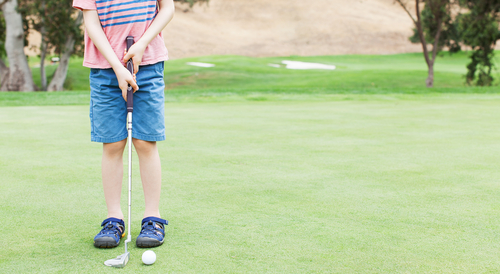 Boy learning to play golf on artificial putting green in Albuquerque