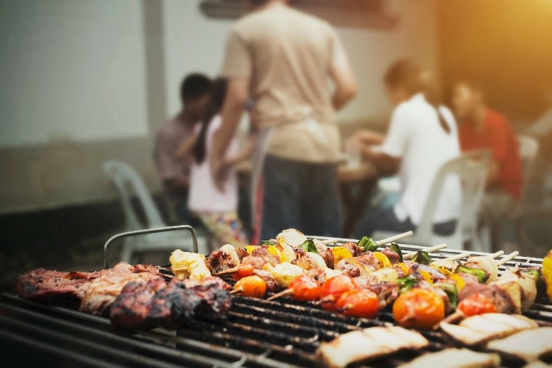People sitting at a table eating grilled food